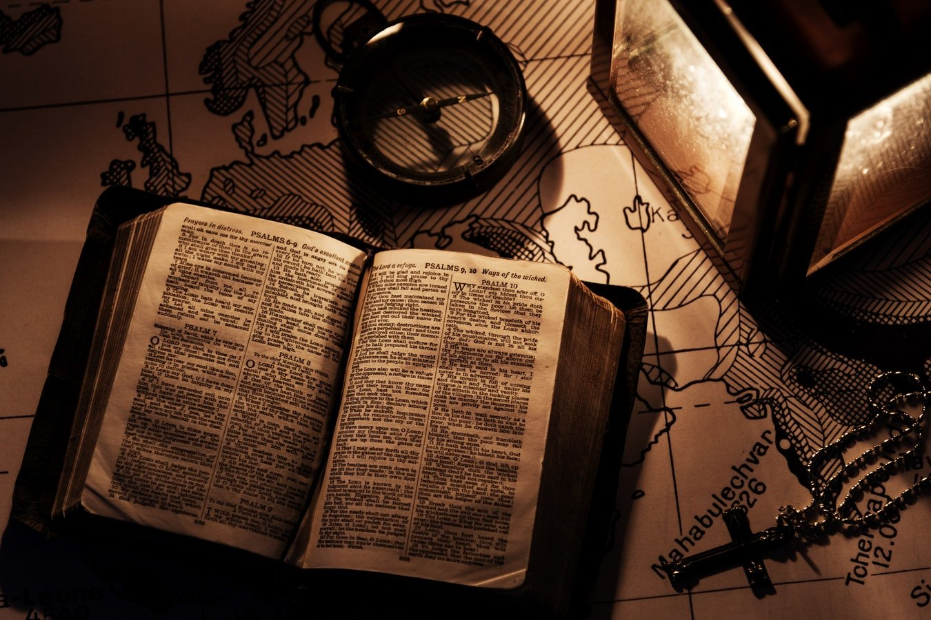 open Bible with compass, lantern and map